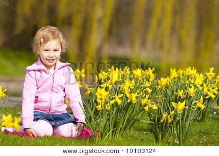 Little girl and daffodils in park