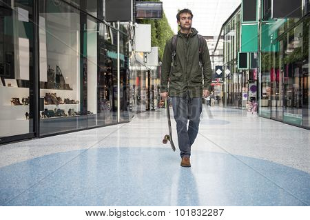 Man, holding a skateboard, strolling casually past the shops at a shopping mall