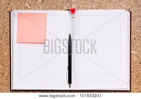 Open notebook with pen on wood background - top view