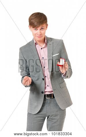 Happy young man holding box with wedding ring, isolated on white background