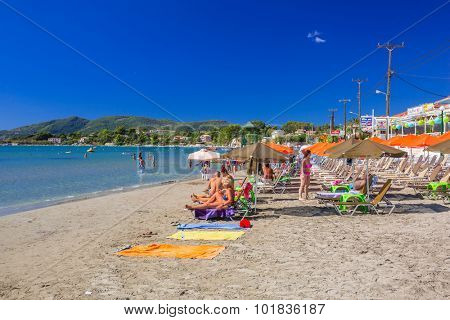LAGANAS, GREECE - AUG 21, 2015: People on the beach of Laganas on Zakynthos island, Greece. Laganas is a very popular holidays destination full of nightclubs, bars, restaurants and souvenir shops.