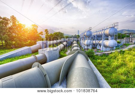 Glow light of petrochemical industry water tank on sunset