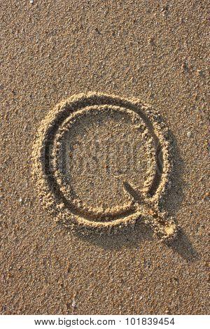 Alphabet's letter Q handwritten in sand on the beach, at sunrise.