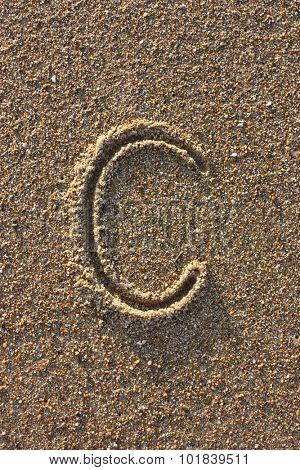 Alphabet's letter C handwritten in sand on the beach, at sunrise.
