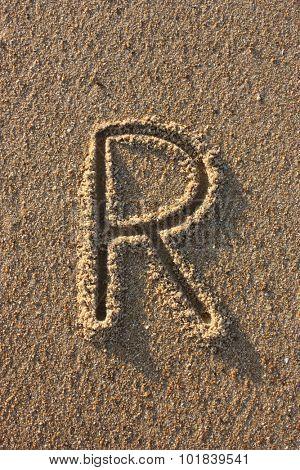 Alphabet's letter R handwritten in sand on the beach, at sunrise.