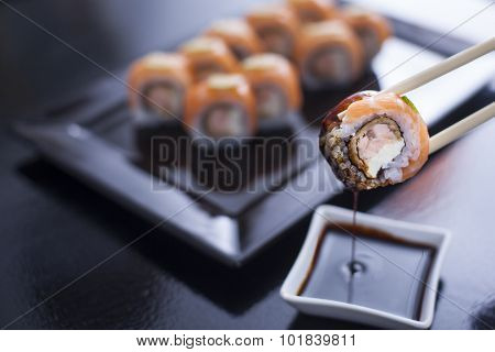 Sushi Roll With Cream Cheese And Fried Salmon. Topped With Raw Salmon And Lime. Being Picked Up With