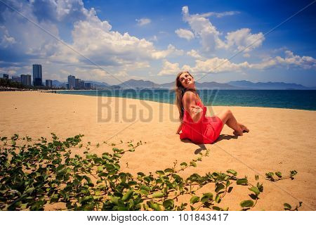Girl In Red Sits On Sand Looks At Sea On Foreground Creepers