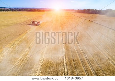 Sunset Above The Combine Working On The Wheat Field