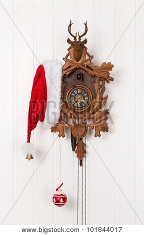 Funny christmas decoration with an old cuckoo clock and a red white santa hat.