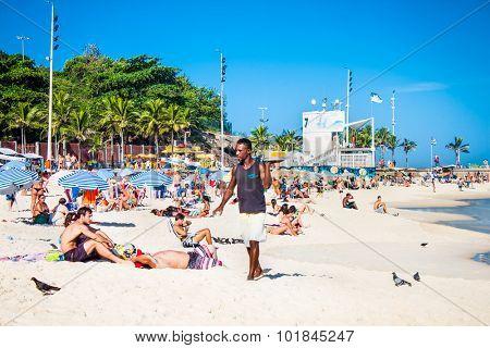 RIO DE JANEIRO, BRAZIL - APRIL 24, 2015: Young Brazilian waiter carrying drinks on April 24, 2015 at Ipanema Beach, Rio de Janeiro. Brazil.