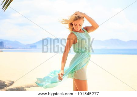 Blonde Girl In Azure Looks Forward Wind Shakes Hair On Beach