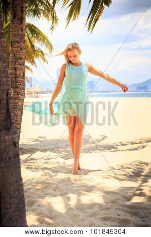 Blonde Girl In Azure With Hands On Breast Near Palms On Beach