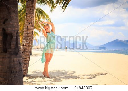 Blonde Girl In Azure With Hands Above Head Near Palms On Beach