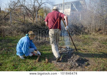Couple Sustains Combustion Of Bonfire In Autumnal Rural Garden.