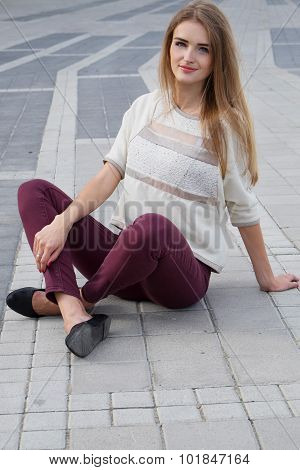 Cute Blonde Girl With Long Hair Sitting On The Floor