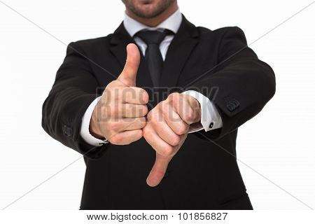 Businessman' hands giving a thumbs up and down close-up