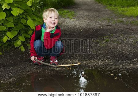 Young Boy Playing At A Puddle