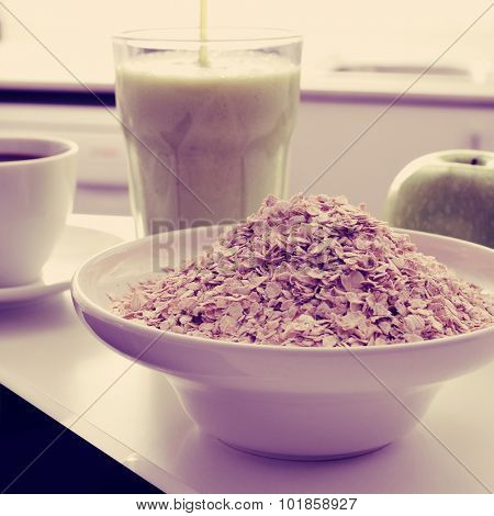 a bowl with oatmeal cereal, a cup of coffee, an apple and a glass with a green smoothie on the kitchen table, with a filter effect