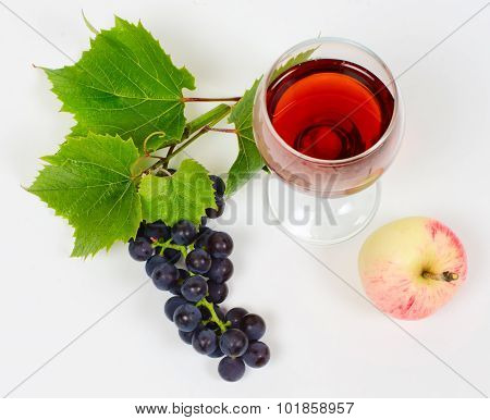 The Cluster Of Grapes And Apple Lie Near A Wine Glass With Brandy