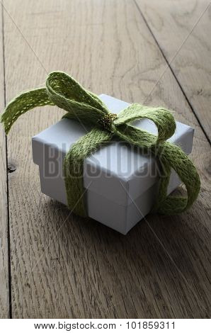 White Gift Box With Soft Green Ribbon On Old Wood Table