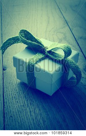 White Gift Box With Green Ribbon On Wood Table - Cross Processed