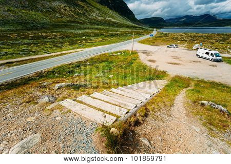 Asphalt country road in the mountains in Norway. Cars are on the