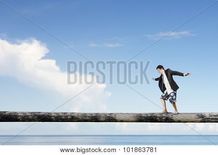 Man Balancing On Tree Trunk High In The Sky