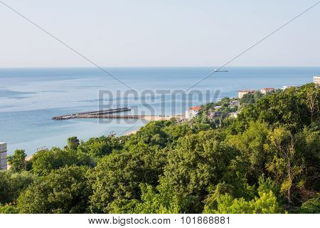 Sea vie , barge , pier, forest on the shore and houses with red tile roofs