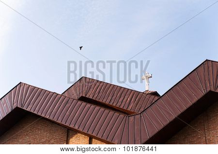 Metal white cross on red roof of church
