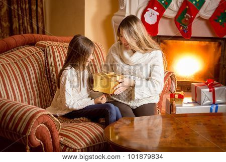 Mother And Daughter Unpacking Christmas Present At Fireplace