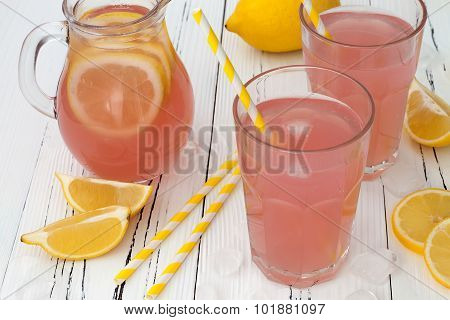 Refreshing pink lemonade on white old vintage wooden background