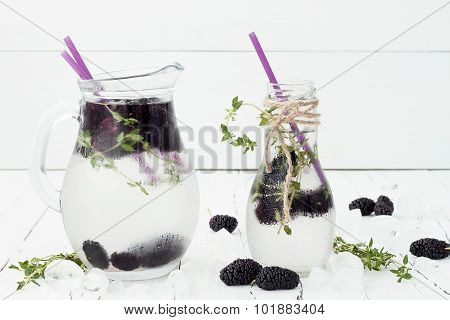 Healthy detox water with mulberry. Cold refreshing berry drink with ice and thyme on white wooden ta