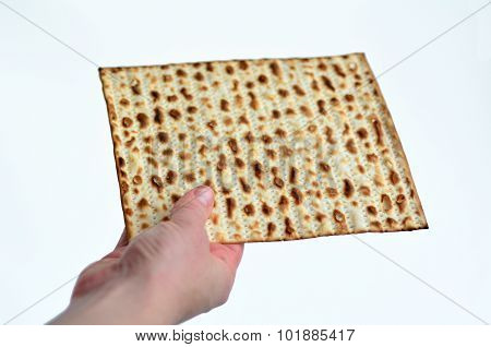 Jewish woman hand holds leavened bread matza on white background with copy space