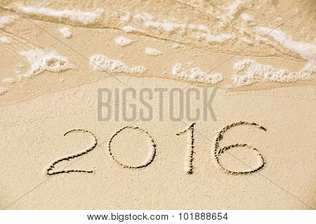 2016 Inscription Written In The Wet Yellow Beach Sand Being Washed With Sea Water Wave