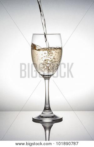 White Wine Pouring Into Wineglass On White Background