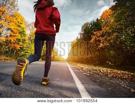 Lady running on the asphalt road through the autumn forest