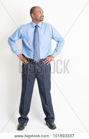 Portrait of full body mature Indian business man hands on waist looking to side, standing on plain background.
