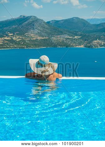Woman by  the edge on the infinity pool enjoying the view in Greece