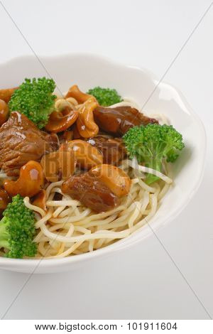 plate of chinese noodles with roasted meat and cashews on white background