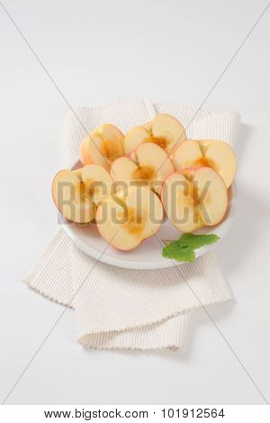 plate of halved and seedless apples on white place mat