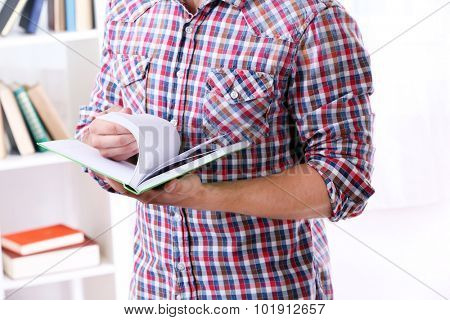 Young man with book in room