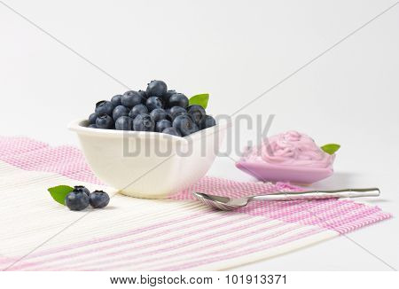 laid table with bowl of fresh blueberries and bowl of blueberry yogurt
