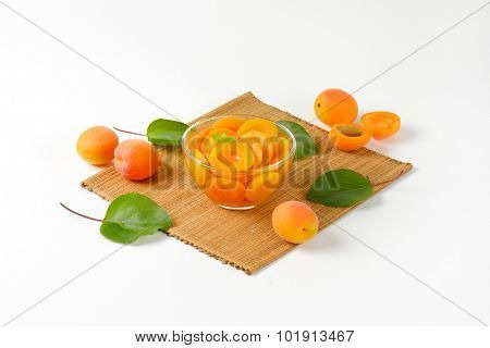 apricot compote with fresh apricots served in the glass bowl on the straw linen