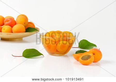 wooden tray with fresh apricots and apricot compote served in the glass bowl