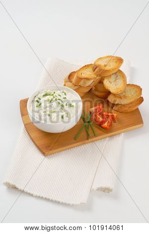 stack of croutons and bowl of chives spread on wooden cutting board and white place mat