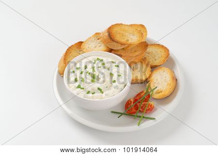 crunchy croutons and bowl of chives spread on white plate