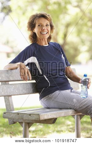 Senior Woman Resting After Exercise In Park