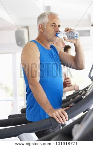 Man On Running Machine In Gym Drinking Water