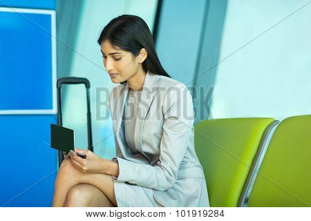 attractive indian business woman looking at her air ticket at airport