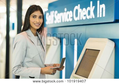 gorgeous indian businesswoman using self help check in machine at airport